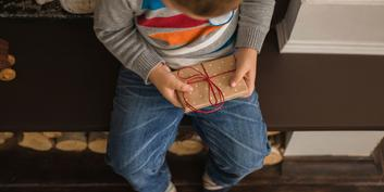 Child holds a gift in his hand.