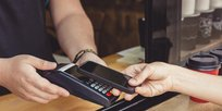 The future of payment: a person paying via TWINT with a cell phone held to a card reader.