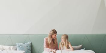 Mom and daughter are sitting at a table talking about money.