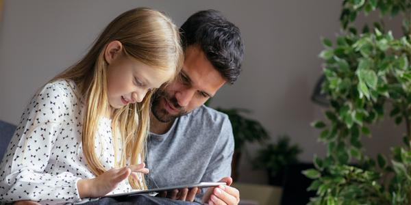 Father and daughter learning everything about money on the tablet.