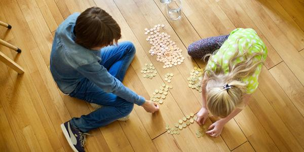 Boy and girl counting money on the floor