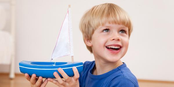 Smiling boy with a toy sailboat