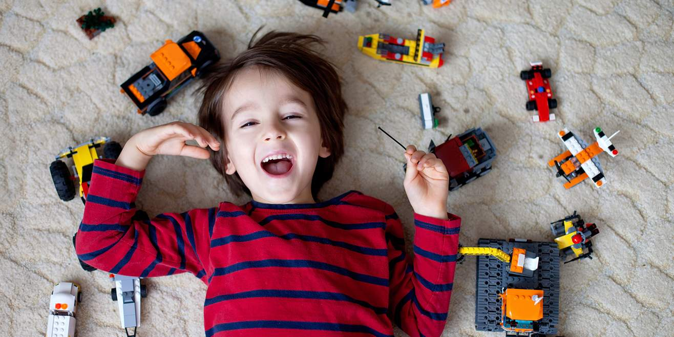 Smiling boy surrounded by toys on the floor