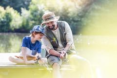 Father explains something to son while fishing.