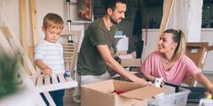 Parents with child unpacking moving boxes.