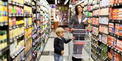 Child walking down supermarket aisle with mom