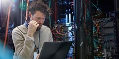 header image showing man looking at laptop in a data center